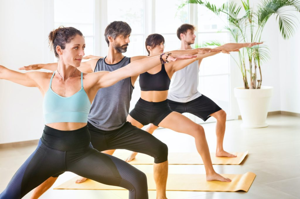 Group of people in warrior yoga pose