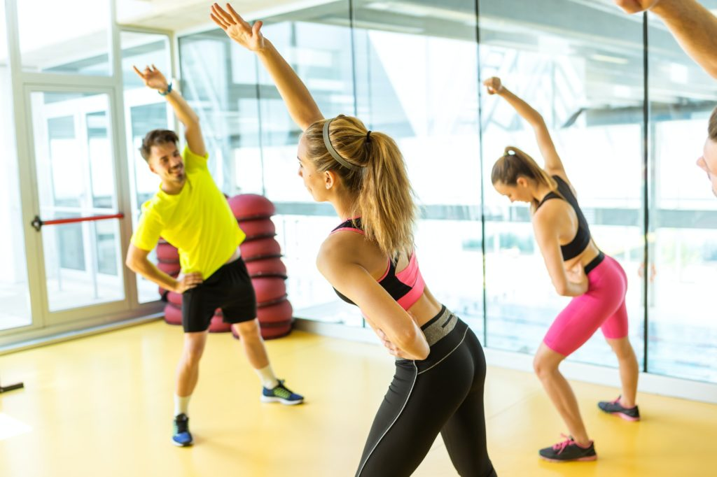 Group of sporty people doing aerobic class on a fitness center.