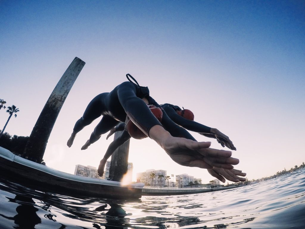 Two swimmers wearing wetsuits diving into the ocean to train in open water.